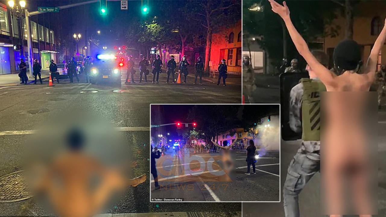 Protestuesja lakuriq para agjentëve të policisë, por me maskë anti-covid 19